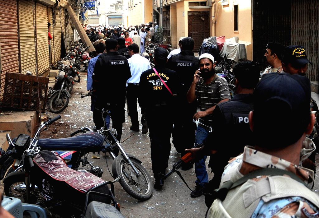 Policemen inspect the bomb blast site in southern Pakistani port city of Karachi, March 20, 2015. At least two people were killed and seven others injured when a ...
