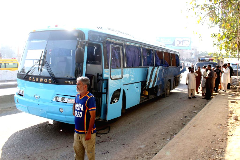 People gather around a damaged bus at the blast site in southern Pakistani port city of Karachi, March 27, 2015. At least two policemen were killed and 13 others ...