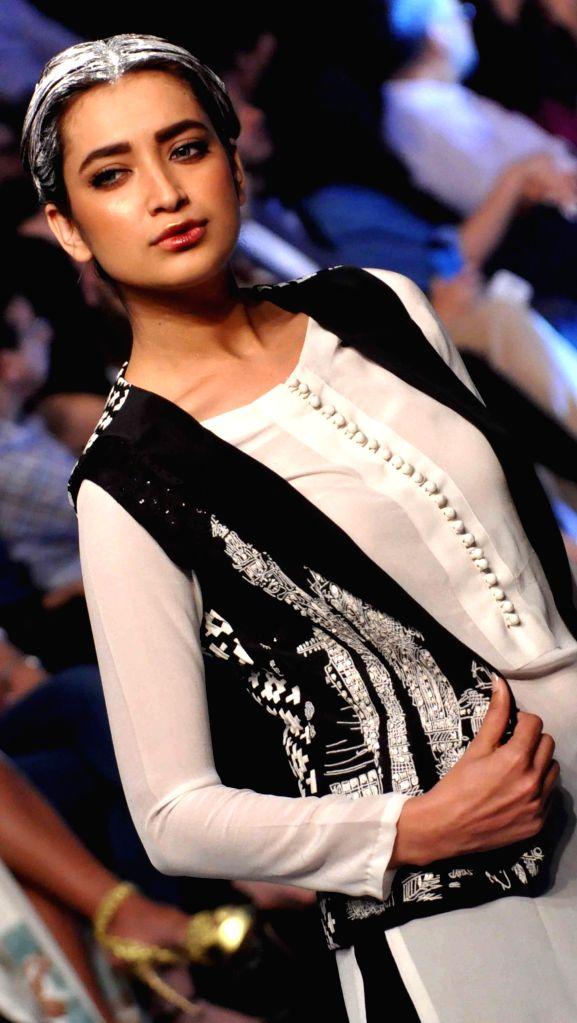 Karachi (Pakistan): A model presents a creation by fashion designer Adnan Pardesy on the second day of Pakistan Fashion Week in Karachi, Pakistan, on Nov. 26, 2014. The three-day Pakistan Fashion ...