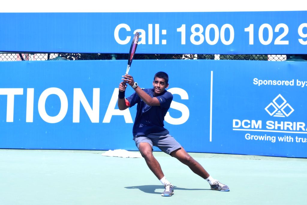 Karan Singh in action against Bushan Haobam in Boys U-16 category of the Fenesta Open Junior National Tennis Championship, in New Delhi on Oct 9, 2019. - Karan Singh