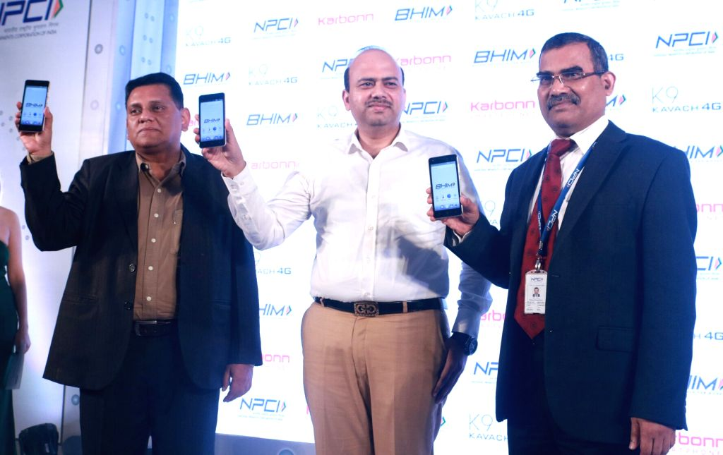 Karbonn Mobiles Executive Director Shashin Devsare, Director Ashish Aggarwal and NPCI CEO A P Hota at the launch of Karbonn K9 Kavach with BHIM app Integration in New Delhi, on July 4, ...