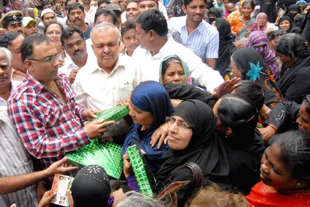 Karnataka cabinet ministers Ramalinga Reddy and Dinesh Gundu Rao distribute new clothes to Muslims during Ramadan in Bangalore on July 20, 2014. - Ramalinga Reddy and Dinesh Gundu Rao