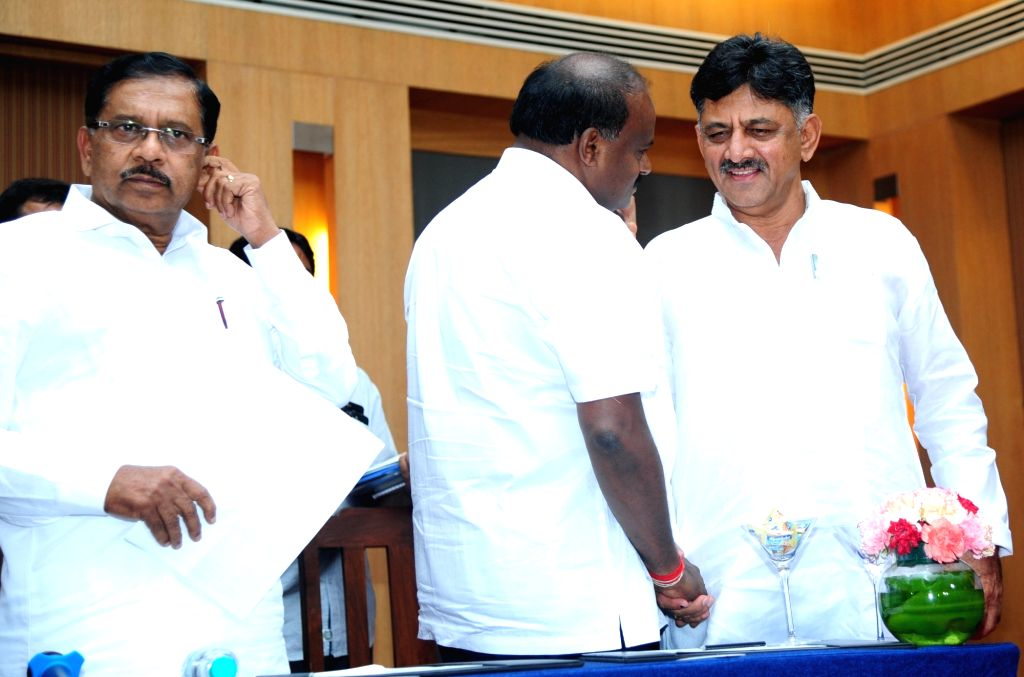 Karnataka Chief Minister and JD-S leader HD Kumaraswamy interacts with Congress MLA DK Shivakumar during a joint press conference in Bengaluru on June 1, 2018.