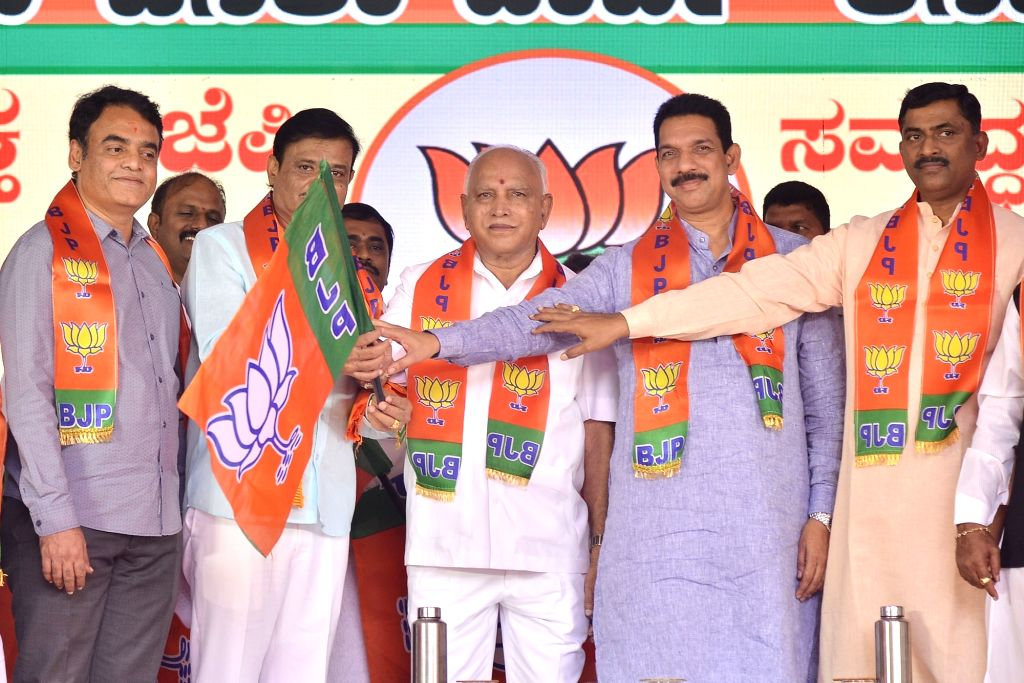 Karnataka Chief Minister B. S. Yediyurappa, BJP State President Nalin Kumar Kateel and party National Secretary Muralidhar Rao hand over the party flag to disqualified MLA Munirathna ... - B. S. Yediyurappa, Nalin Kumar Kateel and Secretary Muralidhar Rao