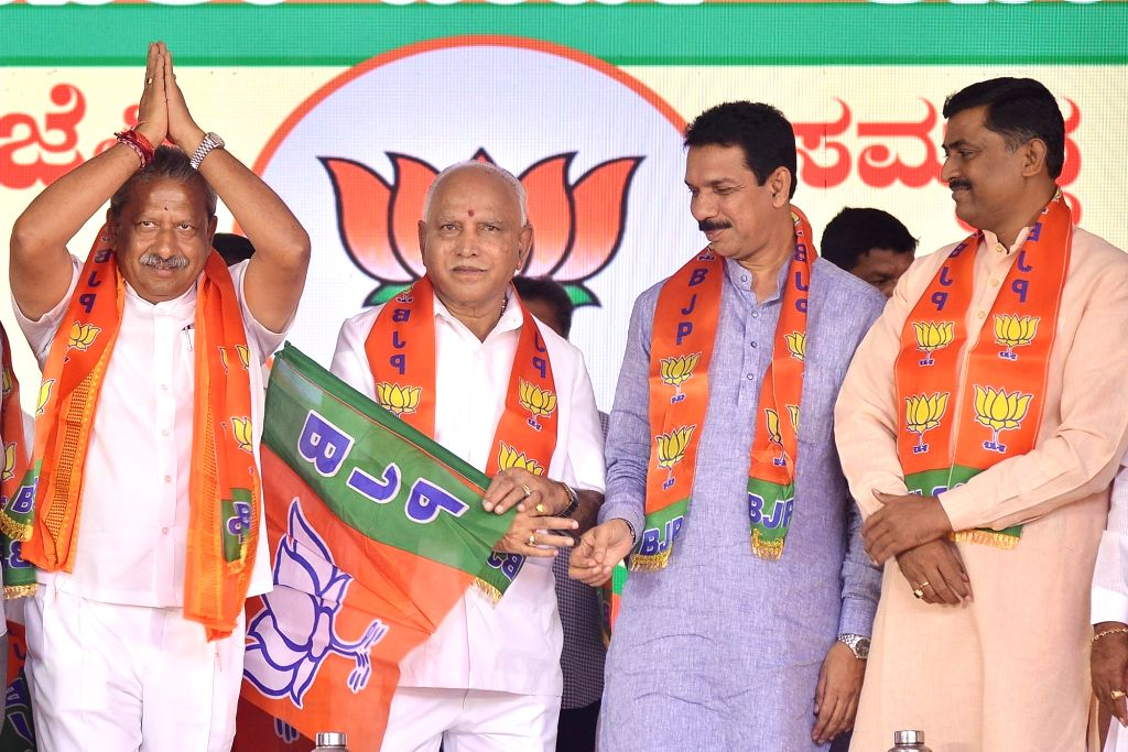 Karnataka Chief Minister B. S. Yediyurappa, BJP State President Nalin Kumar Kateel and party National Secretary Muralidhar Rao hand over the party flag to disqualified MLA Byrathi ... - B. S. Yediyurappa, Nalin Kumar Kateel and Secretary Muralidhar Rao