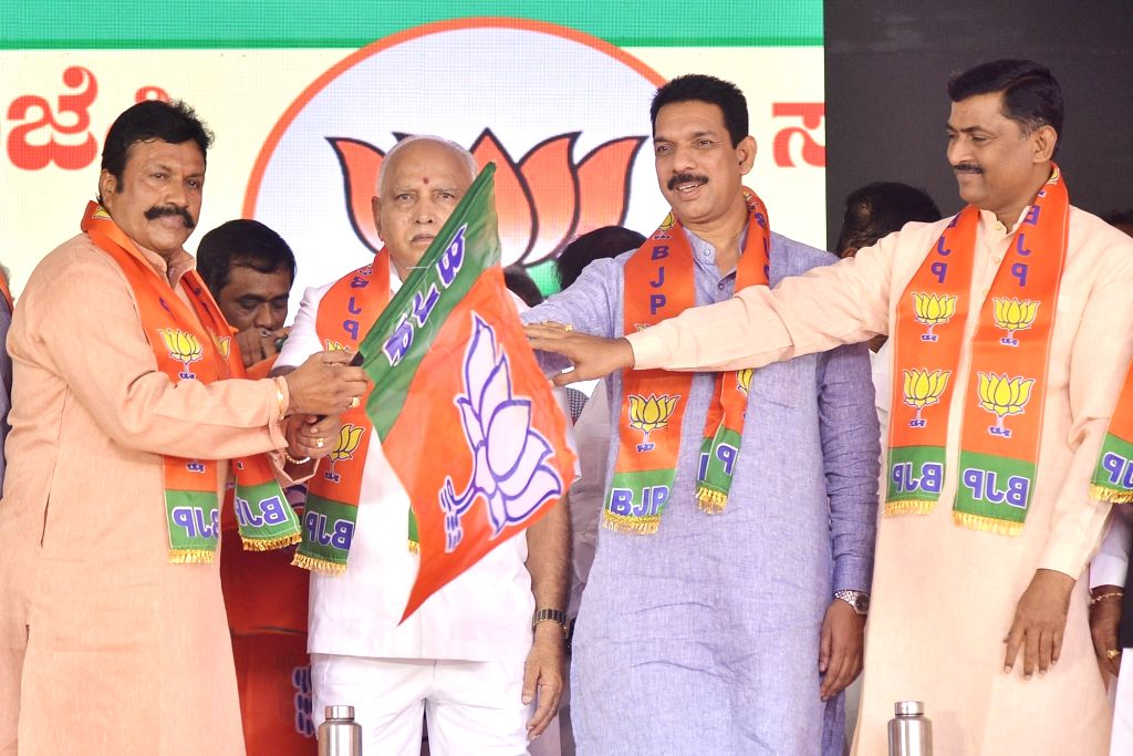 Karnataka Chief Minister B. S. Yediyurappa, BJP State President Nalin Kumar Kateel and party National Secretary Muralidhar Rao hand over the party flag to disqualified MLA BC Patil during ... - B. S. Yediyurappa, Nalin Kumar Kateel and Secretary Muralidhar Rao