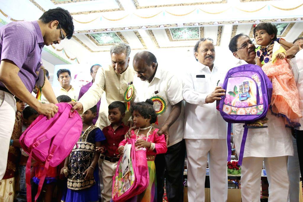 Karnataka Chief Minister H. D. Kumaraswamy and Deputy Chief Minister G. Parameshwara distribute school bags among children at the inauguration of Karnataka Public School, in Bengaluru on ... - H. D. Kumaraswamy