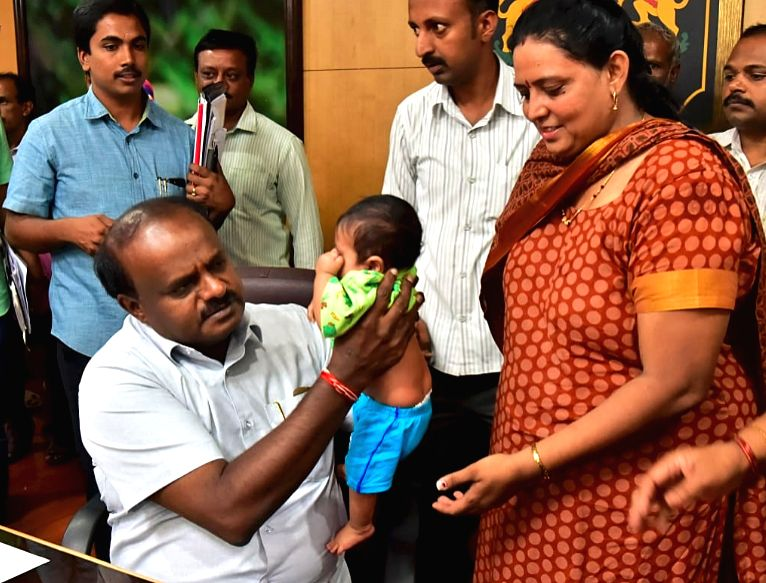 Karnataka Chief Minister H. D. Kumaraswamy holds a child whose mother lost her right arm in accident during 'Janatha Darshana', in Bengaluru on June 7, 2018. - H. D. Kumaraswamy