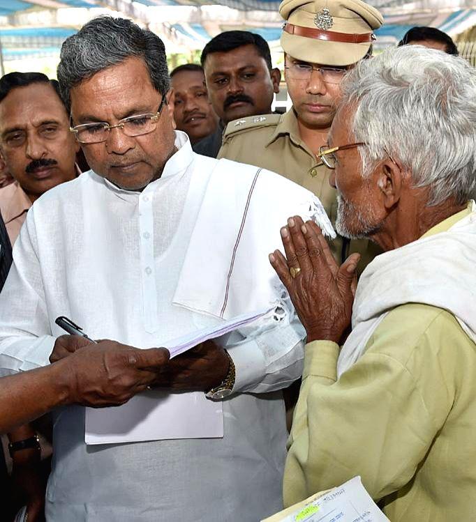 Karnataka Chief Minister Siddaramaiah interacts with public during his `janata darshan` in Bangalore on Sept 2, 2014. - Siddaramaiah