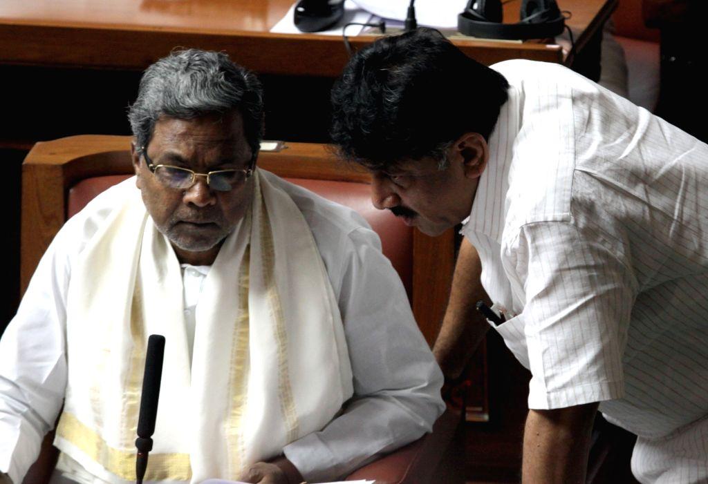 Karnataka Chief Minister Siddaramaiah interacts with legislature D K Shivakumar on the first day of Winter Assembly Session at Vidhan Soudha, in Bengaluru on Nov. 16, 2015. - Siddaramaiah