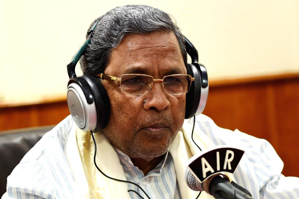 Karnataka Chief Minister Siddaramaiah speaks in a microphone during a programme on Akashavani FM Radio station, in Bengaluru on July 2, 2016. - Siddaramaiah