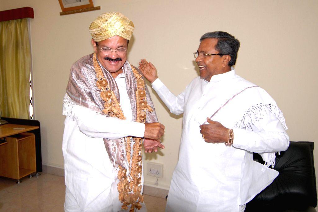 Karnataka Chief Minister Siddaramaiah with Union Minister for Urban Development, Housing and Urban Poverty Alleviation and Parliamentary Affairs M. Venkaiah Naidu during a courtesy meeting in ... - M. Venkaiah Naidu