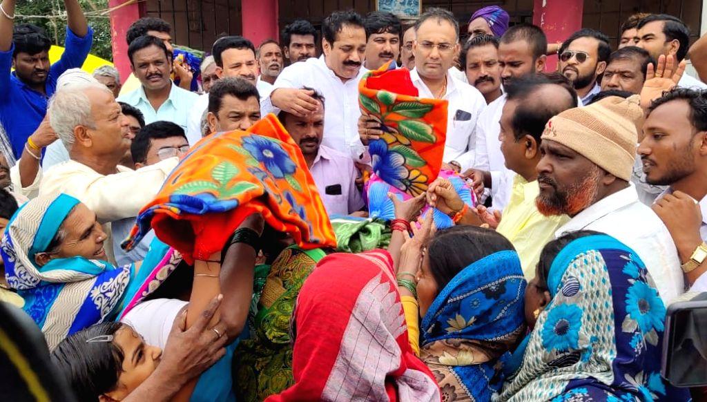 Karnataka Congress chief Dinesh Gundu Rao distributes relief material among flood victims during his visit to Karnataka's flood affected Hubballi, on Aug 10, 2019. - Dinesh Gundu Rao