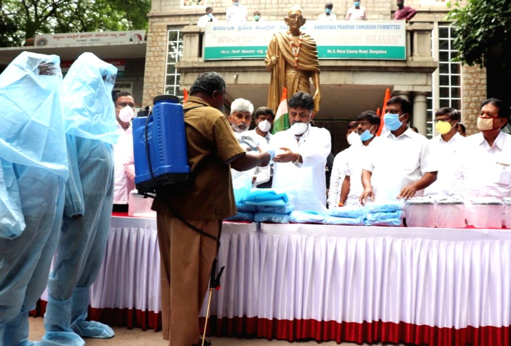 Karnataka Congress President DK Shivakumar distributes PPE kits to sanitation and municipal workers at Congress Bhavan in Bengaluru during the extended nationwide lockdown imposed to ...