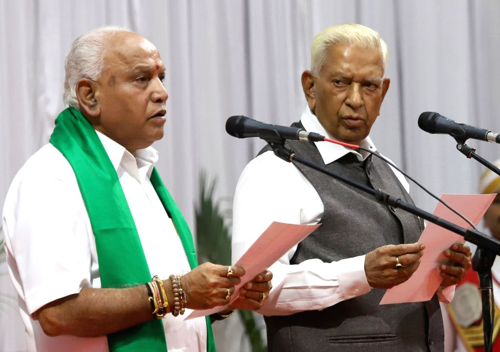 Karnataka Governor Vajubhai Vala administers the oath of office to the state's BJP President B. S. Yediyurappa as Karnataka's new Chief Minister, during a swearing-in ceremony at Raj ...