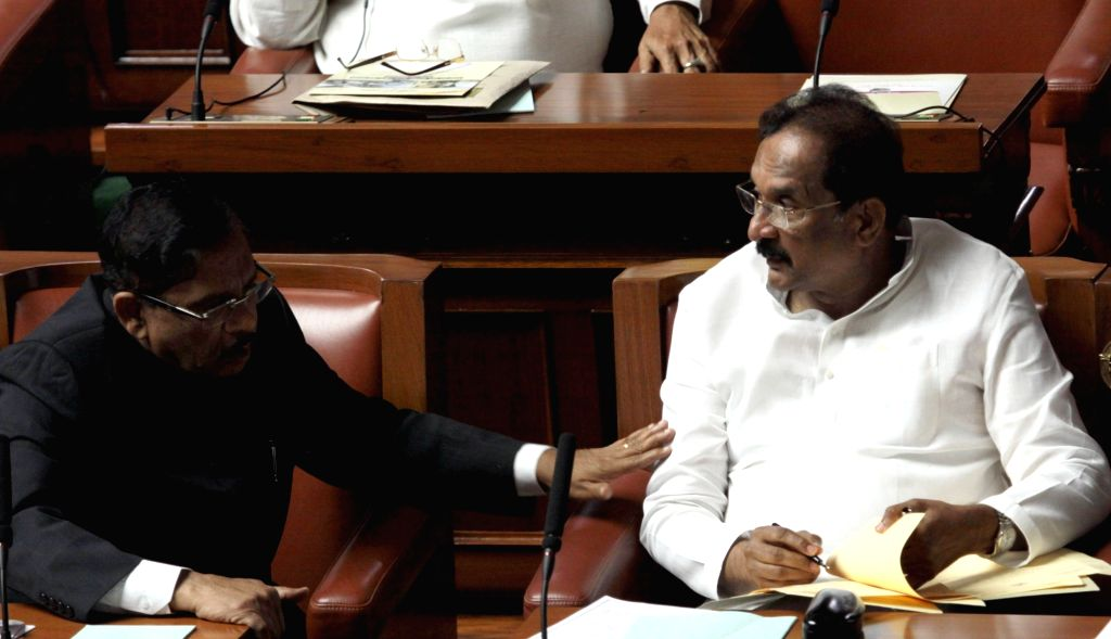Karnataka Home Minister Dr G Parameshwar interacts with legislature K J George on the first day of Winter Assembly Session at Vidhan Soudha, in Bengaluru on Nov. 16, 2015.