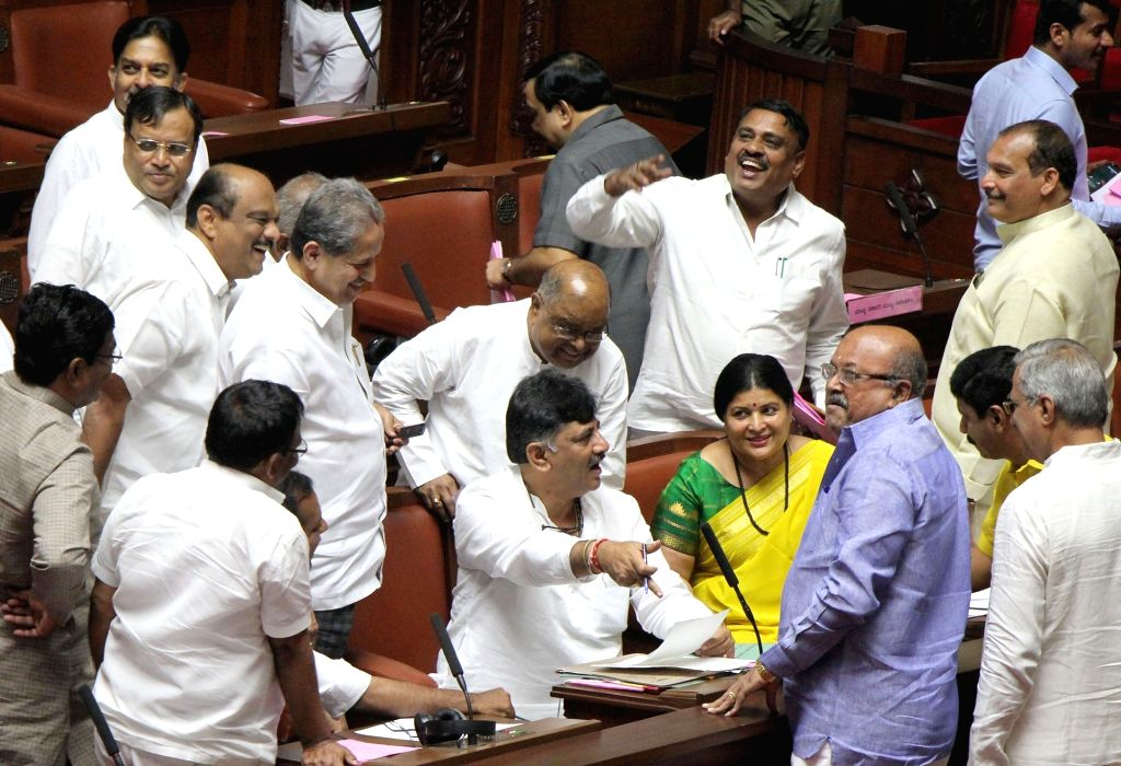 Karnataka Minister D. K. Shivakumar interacts with Congress MLCs during the Karnataka Legislative Council Session at the state assembly, in Bengaluru on July 16, 2019. - D. K. Shivakumar