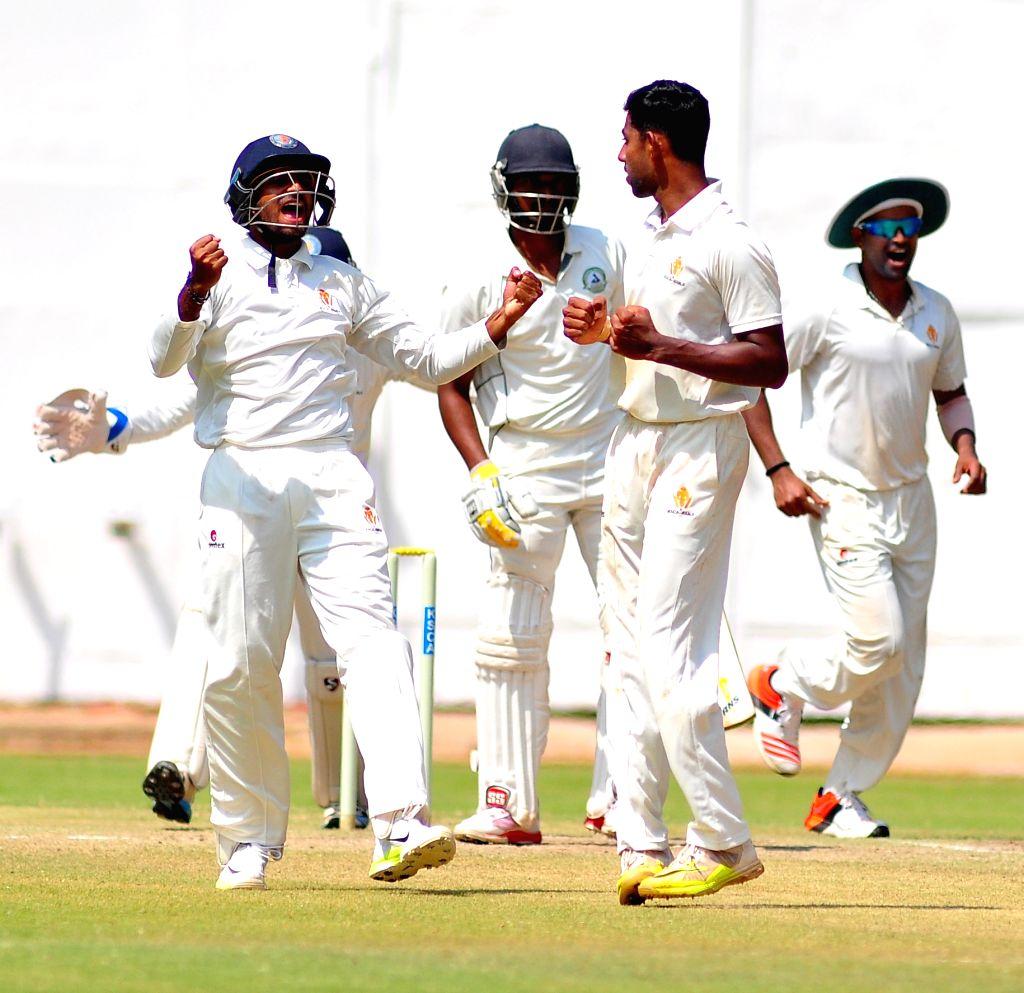 Karnataka players celebrate fall of a wicket during the Ranji Trophy Match between Vidharba and Karnataka at Chinnaswamy Stadium, in Bangalore on Oct 17, 2015.