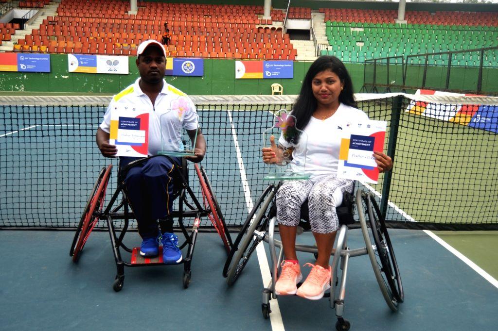 Karnataka's men's singles winner Shekar Veeraswamy (left) and Karnataka's women's singles winner Prathima Rao (right) in their wheel-chairs at the state lawn tennis court in Bengaluru's ... - Prathima Rao