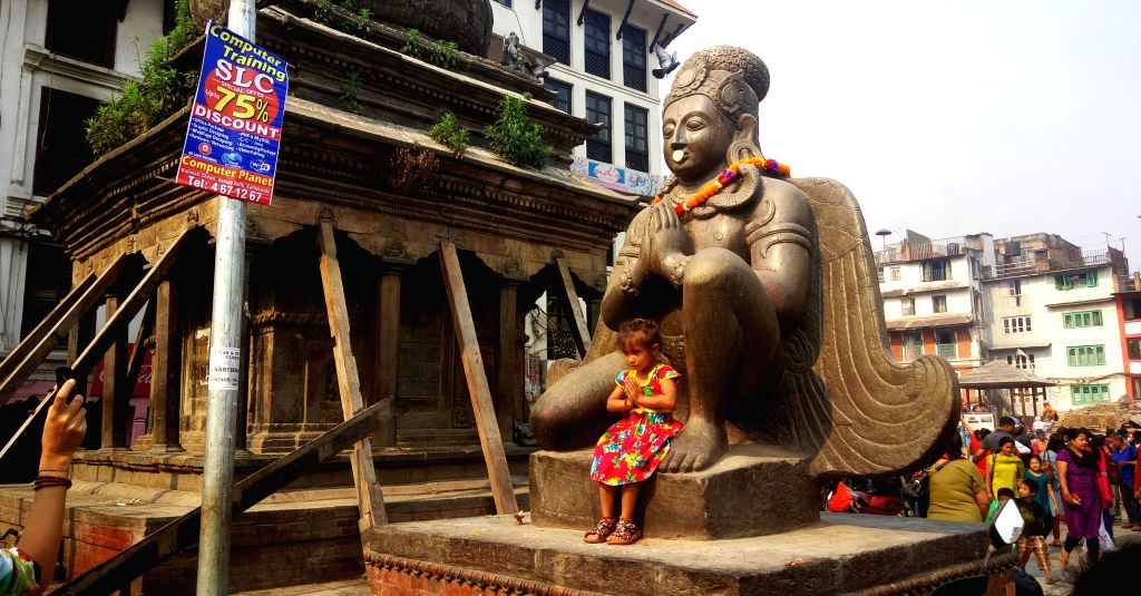 KATHMANDU, April 18, 2016 - A girl gestures in front of the Idol of Garud at the remains of Kastamandap Temple damaged during the April 25 earthquake last year in Kathmandu, capital of Nepal, on ...