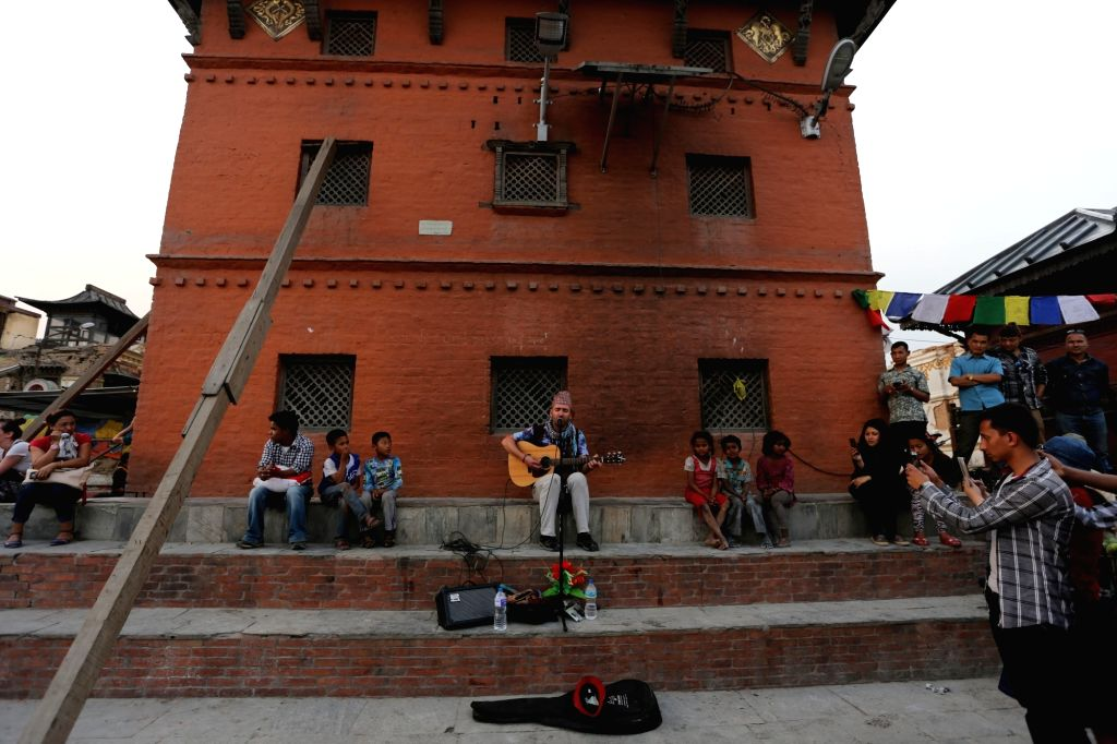 KATHMANDU, April 21, 2016 - A foreign singer (C) sings Nepali songs to collect money for the education-deprived children and earthquake-effected villages at Swayambhunath in Kathmandu, Nepal, April ...