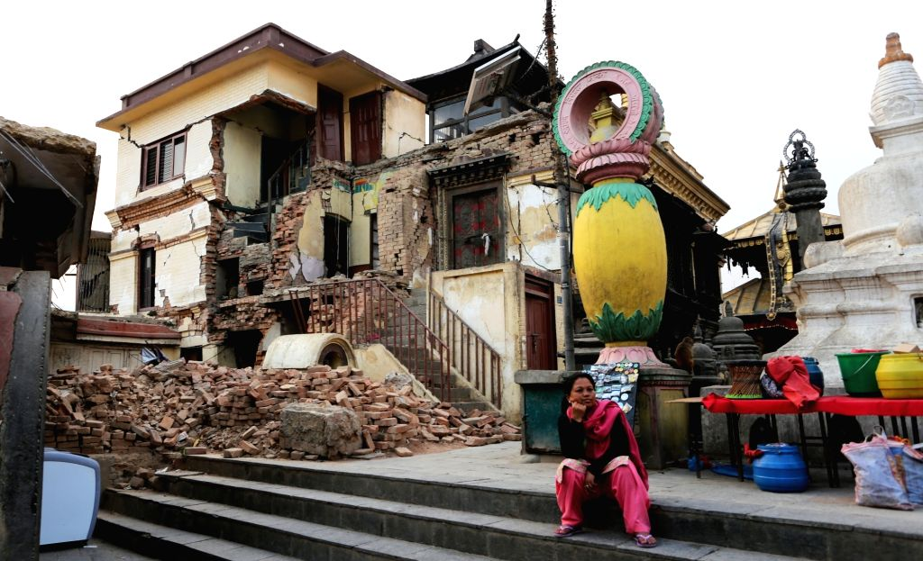 KATHMANDU, April 21, 2016 - A Nepalese woman rests in front of a damaged monastery at the world heritage Swayambhunath Stupa, or monkey temple, in Kathmandu, Nepal, April 20, 2016. Reconstruction ...