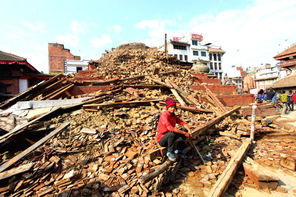 A man sits near a damaged temple after a massive earthquake in Kathmandu, Nepal, April 27, 2015. A total of 3,218 people had been killed and about 6,500 others ...