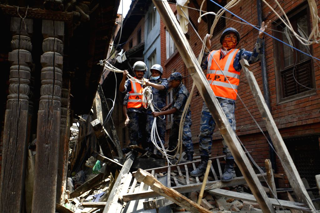Members of the Nepalese Armed Police Force try to rescue people stuck in houses in Bhaktapur, Nepal, April 26, 2015. A total of 3,218 people had been killed and ...