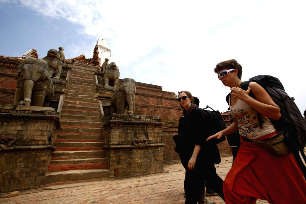 Tourists pass through a collapsed temple in Bhaktapur, Nepal, April 26, 2015. A total of 3,218 people had been killed and about 6,500 others injured in the ...