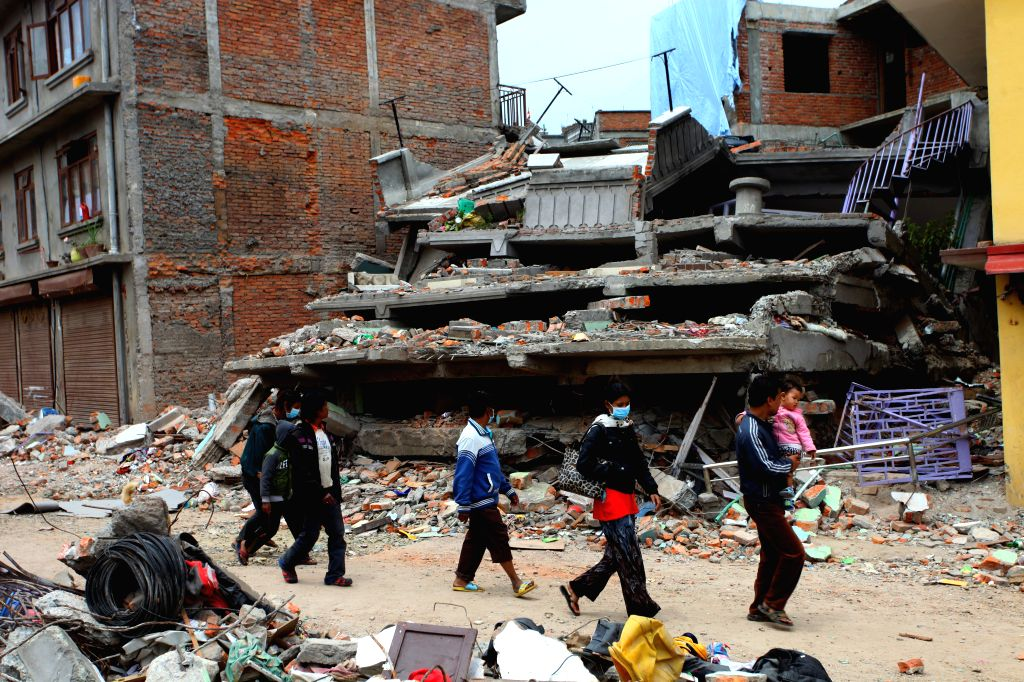 People walk near the debris of fallen buildings in Kathmandu, Nepal, April 28, 2015. The death toll from a powerful earthquake in Nepal climbed to 4,555 and a ...