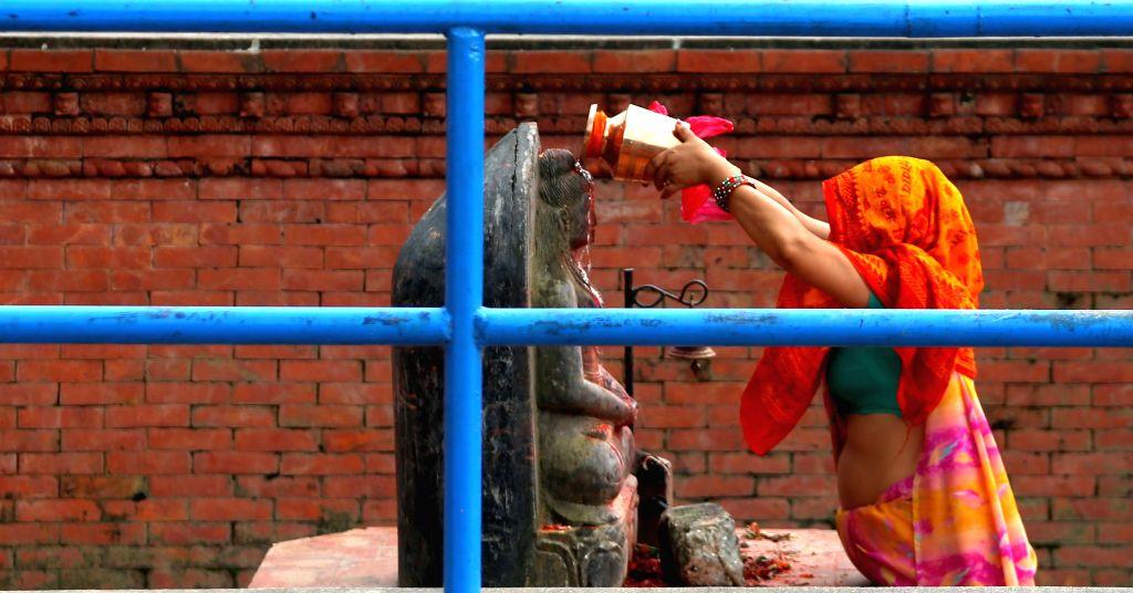 KATHMANDU, Aug. 16, 2016 - A Hindu devotee offers prayer at the premises of Shiva temple on the last day of Shrawan Somvar at Tokha Chandeshwari village in Kathmandu, Nepal, Aug. 15, 2016. Mondays, ...