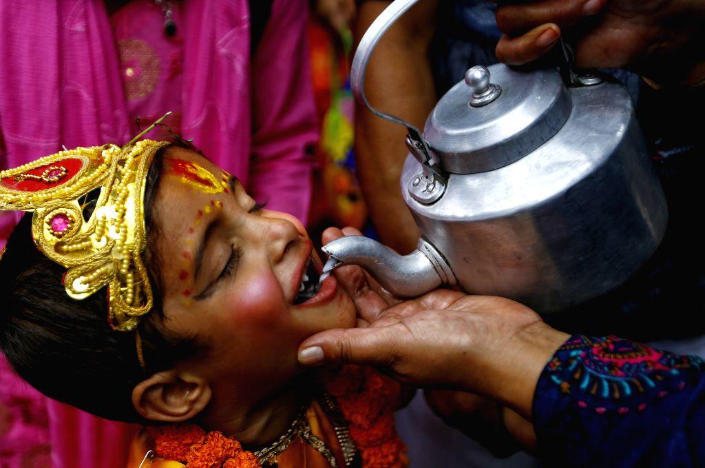 KATHMANDU, Aug. 16, 2019 - A boy in traditional attire drinks milk in a procession during the Gaijatra festival, or festival of cows, in Kathmandu, Nepal, Aug. 16, 2019.