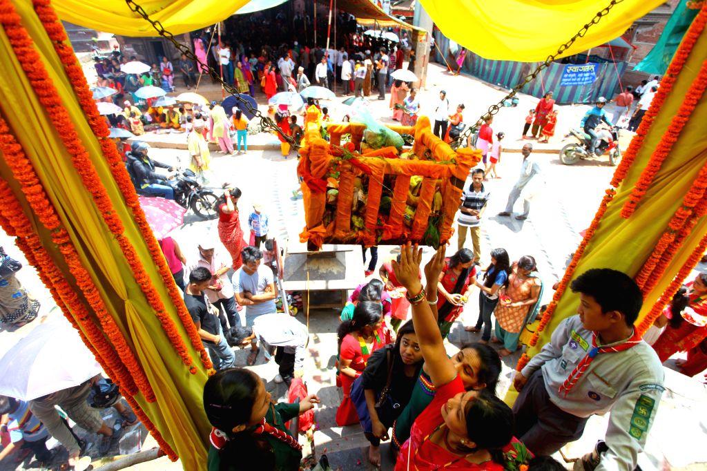 "Hindu devotees move the ""Jhula"" of Lord Krishna ""Balgopal"" while offering their prayers during Krishna Janmasthami festival at Krishna Mandir ."