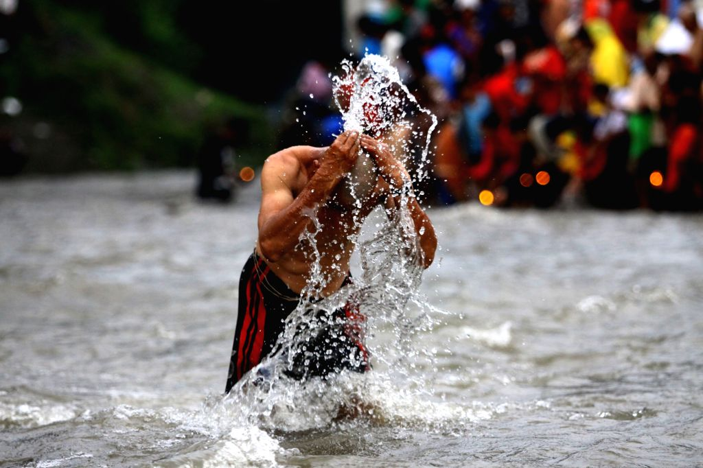 KATHMANDU, Aug. 21, 2017 - A Hindu devotee takes a holy bath before performing religious rituals to celebrate Kuse Aunsi, or Father's Day, on the bank of Bagmati River at Gokarna Temple in Kathmandu, ...