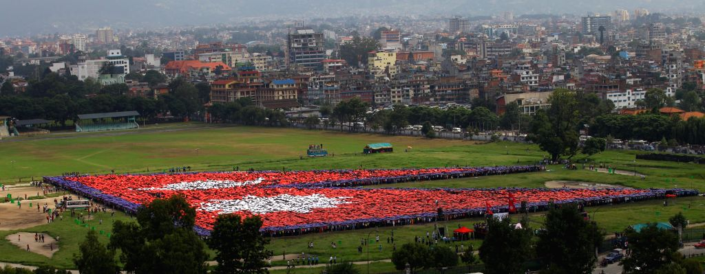 Nepalese people participate in making the largest human-formed National Flag of Nepal to break the Guiness World Record in Kathmandu, Nepal, Aug. 23, 2014. A ...