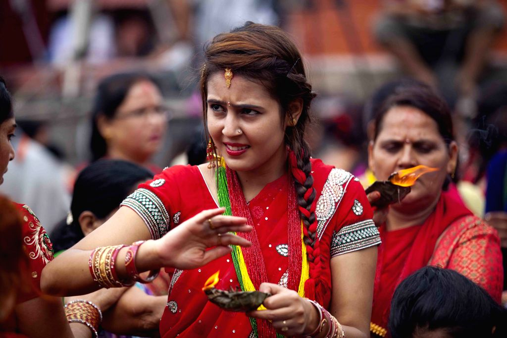 A women is seen lighting oil lamp at Pashupatinath temple during Teej festival in Kathmandu, Nepal, on Aug 27,2014. During the festival , married women fast and ..