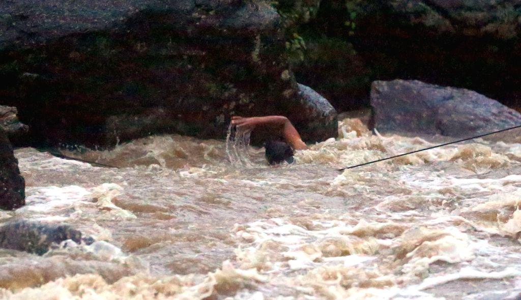 KATHMANDU, Aug. 6, 2018 - A man is in danger in Bagmati river while taking holy bath during the Bol Bom pilgrimage at Sudarijal, Katmandu, Nepal, Aug. 6, 2018.