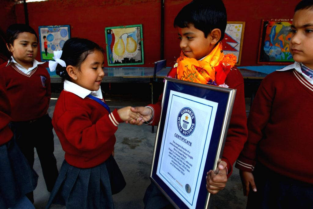 Nepalese eight-year-old kid Saugat Bista (3rd L) is congratulated by his classmates after breaking the Guinness World Records for World's Youngest Director in ...