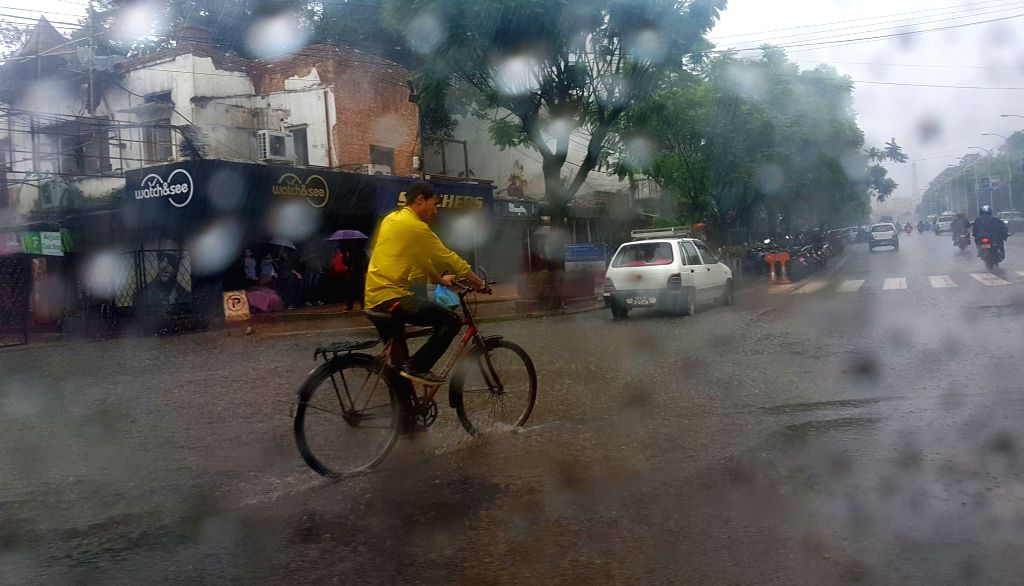 KATHMANDU, July 1, 2016 - A man rides his bicycle in the rain in Kathmandu, Nepal, July 1, 2016. Nepal has been witnessing heavy rainfalls and landslides in various parts of the country. Flights have ...