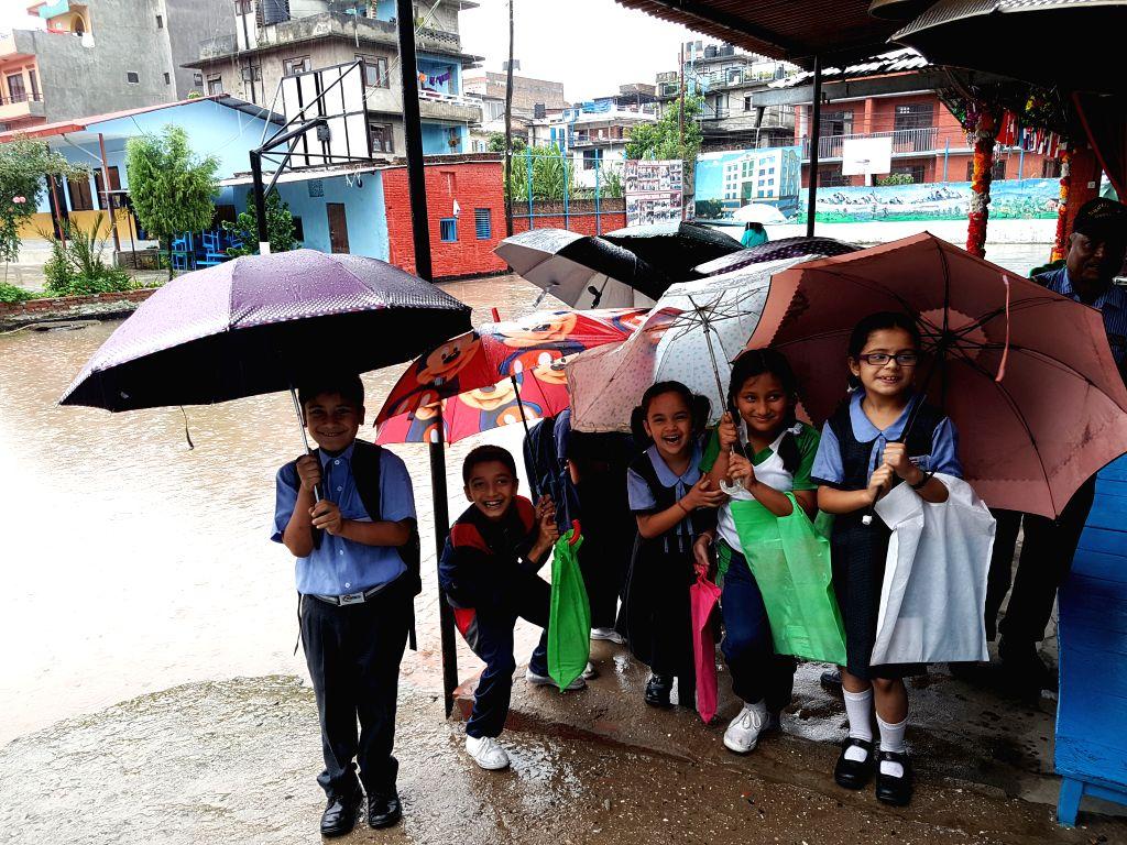 KATHMANDU, July 1, 2016 - School children smile in the rain in Kathmandu, Nepal, July 1, 2016. Nepal has been witnessing heavy rainfalls and landslides in various parts of the country. Flights have ...