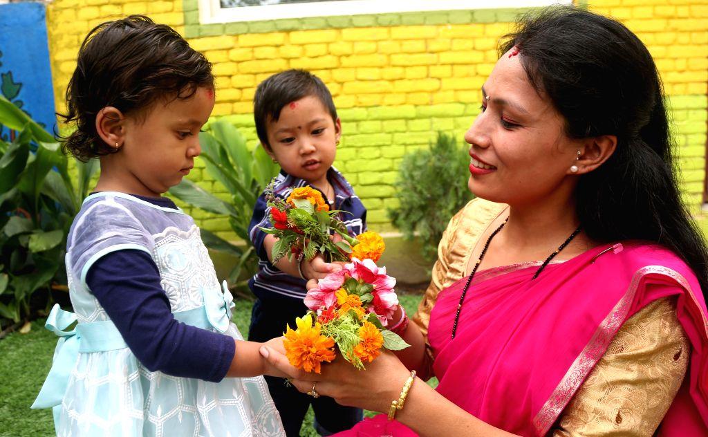 KATHMANDU, July 16, 2019 - School kids offer flowers to their teacher during celebration of Teachers' Day at a local school in Kathmandu, Nepal, July 16, 2019. Teachers' Day, or Guru Purnima ...