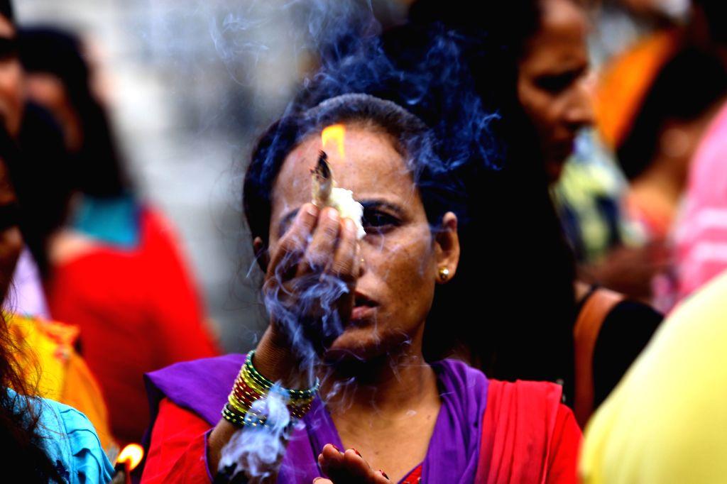A Hindu woman offers prayers on Shrawan Somvar at Pashupatinath temple in Kathmandu, Nepal, July 21, 2014. Shrawan Somvar (Monday) is considered auspicious for ...