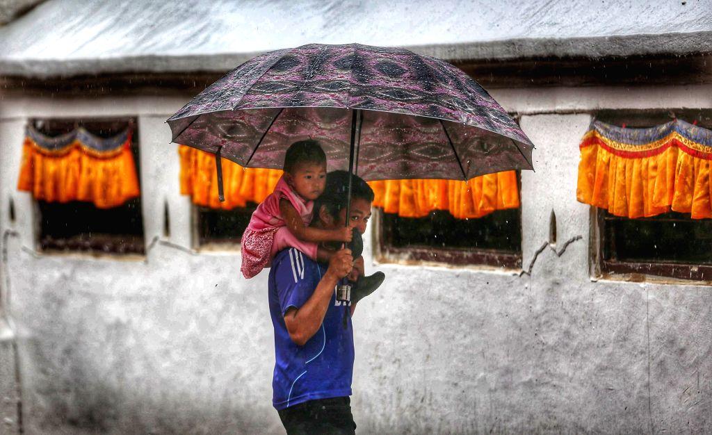 KATHMANDU, July 21, 2019 - A father carrying his kid walks against rainfall at Boudha in Kathmandu, Nepal, July 20, 2019.