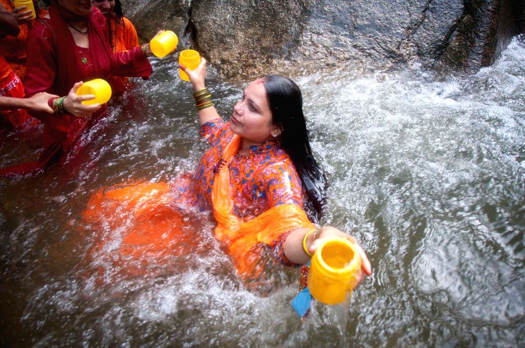 A Nepalese Hindu devotee offers prayers as she takes holy bath before collecting water from the Bagmati river during the Bol Bom pilgrimage at Sudarijaal on the ..