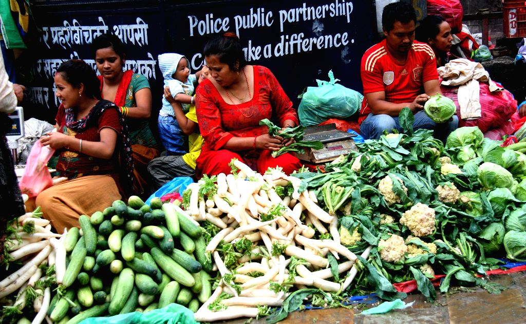 Local vendors wait for customers at a market at Ason in Kathmandu, Nepal, July 24, 2014. Sales of green vegetables and fruits have gone down as media reported ...