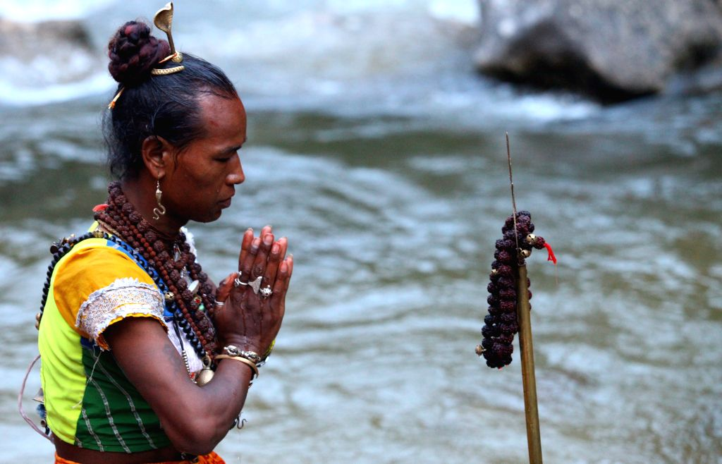 A Hindu devotee is seen offering prayers after taking dip and collecting holy water at Sundarijal participating in the ??Bol Bom?? (or Say Shiva) for Shrawan ...