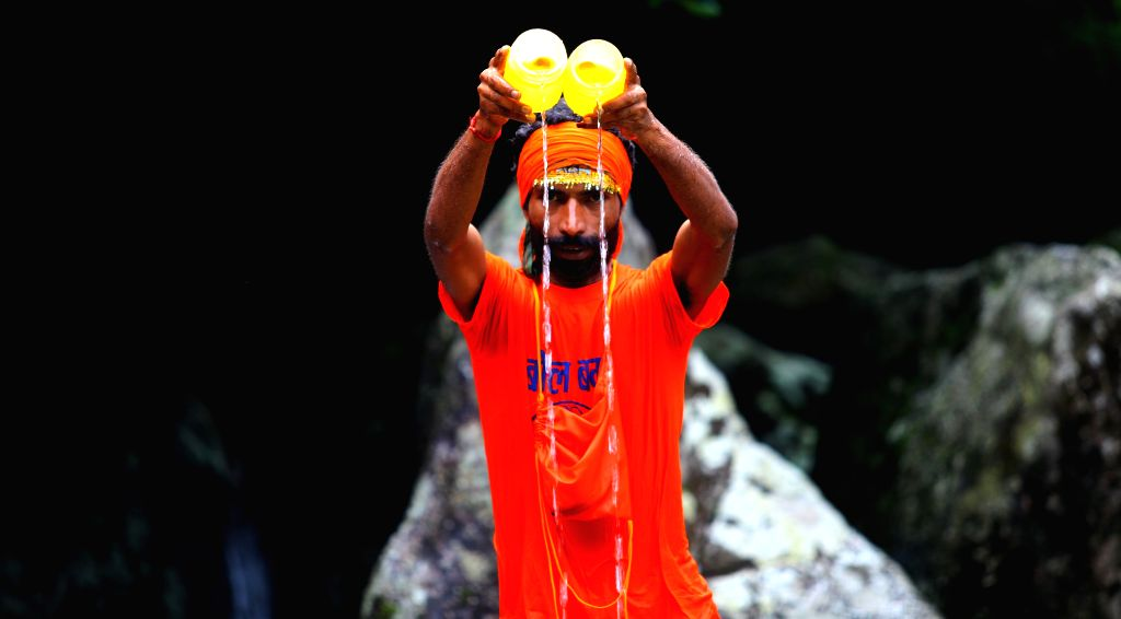 A Hindu devotees offer holy water while walking towards the Pashupatinath Temple from Sundarijal in Kathmandu, Nepal, on July 28, 2014. Devotees run about 15km to