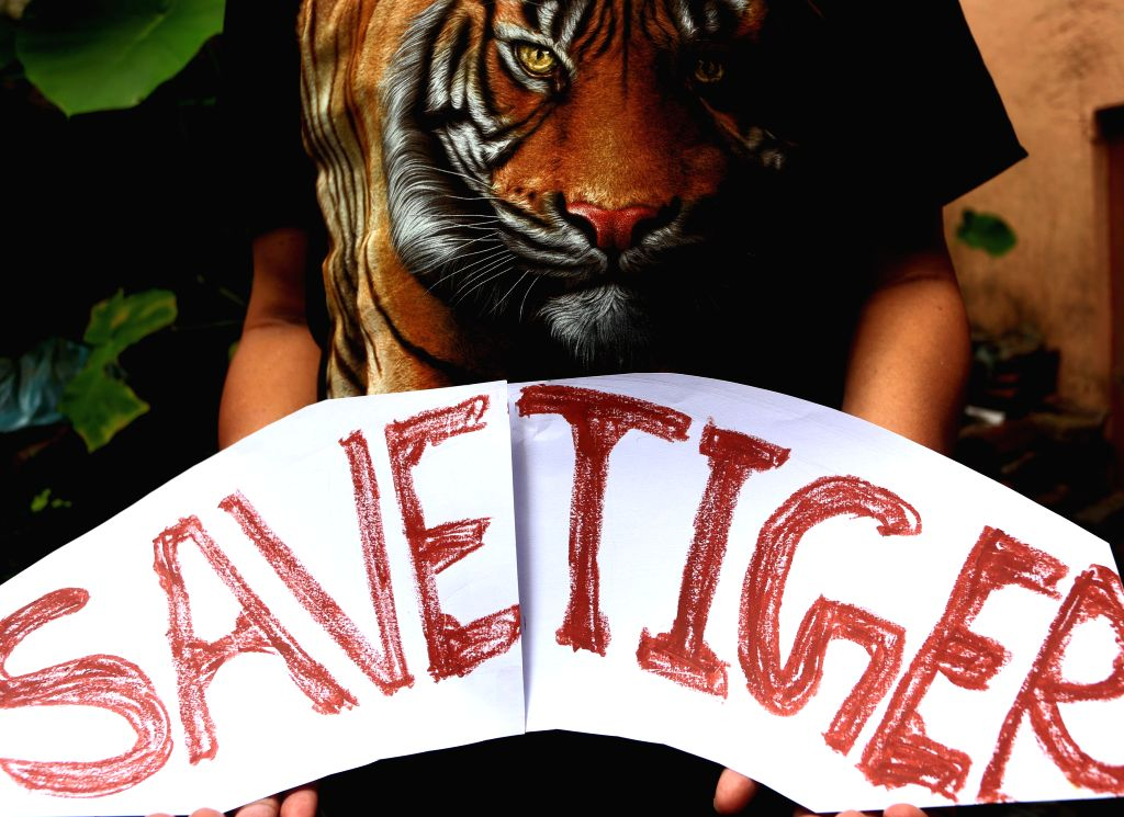 KATHMANDU, July 29, 2018 - A man holds a placard at the Central Zoo of Jawalakhel in Kathmandu, Nepal, July 29, 2018, the International Tiger Day.