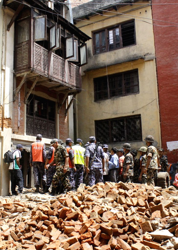 Army and police personnel work at the site of a building collapse in Kathmandu, Nepal, June 28, 2014. At least four workers died and five others were injured ...