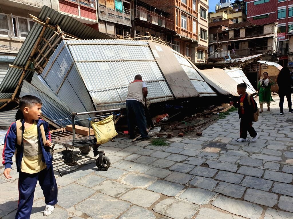 KATHMANDU, June 7, 2019 - People walk past a storm-damaged makeshift house in Kathmandu, Nepal, June 7, 2019. At least one person was killed and 37 others were injured when a strong storm hit several ...
